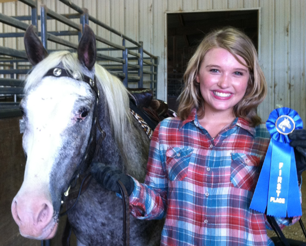 Teenage girl smiling with a blue ribbon and her horse